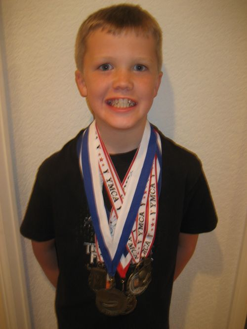 Tyler with some of his Basketball Medals.